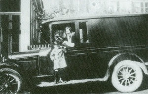 Pelham's first school bus. This photograph shows Thelma Carleton Boutwell driving an early bus with her son, Ralph Boutwell standing on the running board.